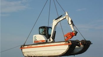 A Wilson Amphibious Bobcat Excavator Fitted with a Pipe Shear is Lifted by a Crane