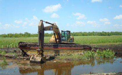 A Wilson Caterpillar Amphibious Excavator Prepares for Levee Construction